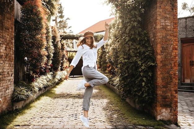 Garota de bom humor está pulando contra o espaço do antigo pátio com ivy na cerca. instantâneo de senhora em roupas brancas.