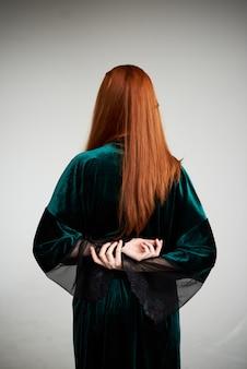 Garota de branco sexy vestido de roupão transparente boudoir em pé com as costas perto da parede