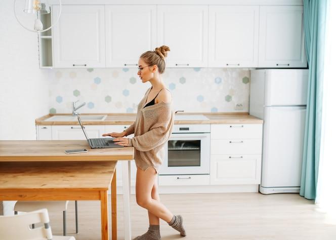 Garota de cabelo comprido justo bela jovem sorridente em copos usando camisola de malha aconchegante usando laptop na cozinha brilhante