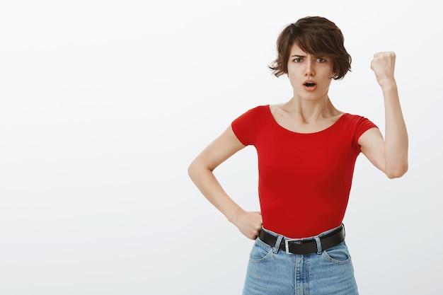 Garota de cabelo curto posando de camiseta vermelha