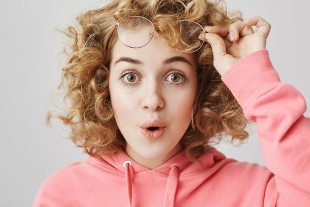 Garota de cabelo encaracolado surpresa tire os óculos e diga uau espantada