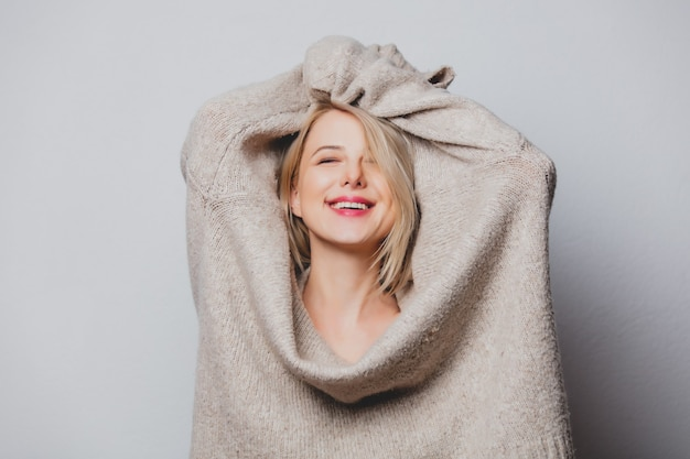 Garota de cabelo loiro em suéter em fundo branco