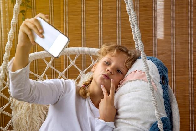 Garota de cabelo loiro tira uma selfie em um telefone celular com um tubarão de brinquedo
