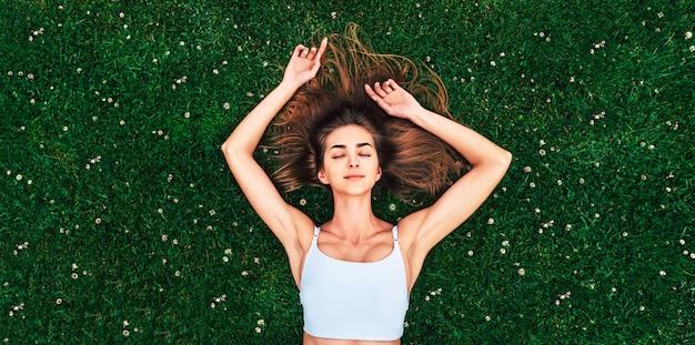 Garota de cabelo muito comprido relaxante na grama ao ar livre