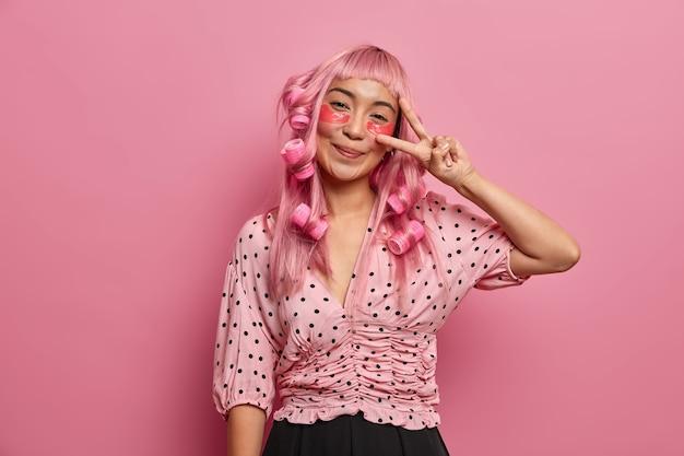 Garota de cabelo rosa feliz aplica tapa-olhos para reduzir as olheiras, faz o sinal da paz, usa modeladores de cabelo para ter cachos perfeitos