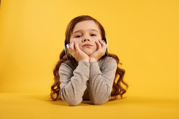 Garota de cabelos, calma vermelha em fones de ouvido apoiado queixo pelas mãos