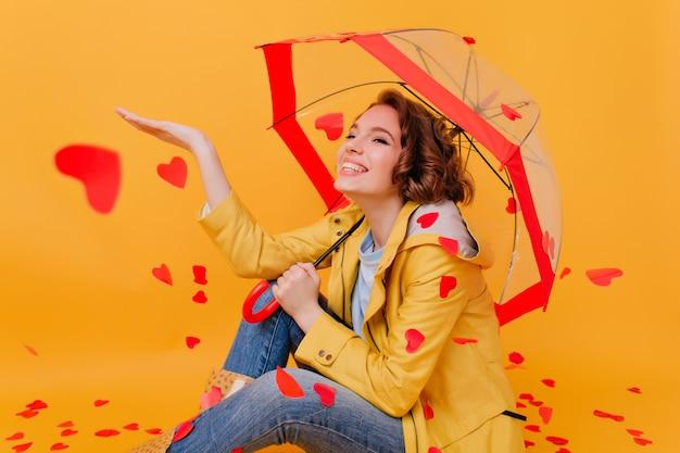 Garota de cabelos castanhos interessada, aproveitando a chuva do coração. mulher atraente sorridente com casaco amarelo, sentada no chão com guarda-sol.