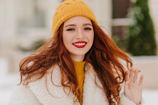 Garota de cabelos compridos em um chapéu amarelo bonito, relaxando em dia frio. jovem muito gengibre, aproveitando o clima de inverno.