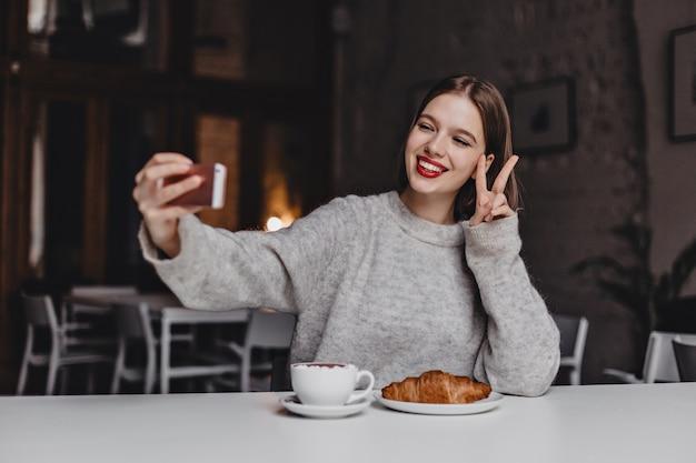 Garota de cabelos curtos positiva com batom vermelho e sorriso branco como a neve faz selfie no café e mostra sinal de paz.