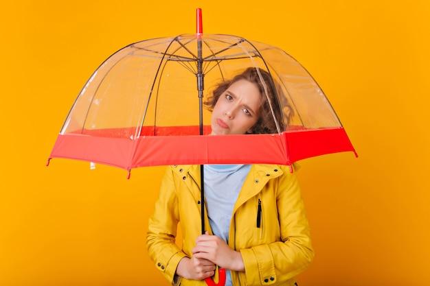 Garota de cabelos escuros chateada posando sob o guarda-chuva. retrato de triste senhora caucasiana em capa de chuva segurando guarda-sol na parede brilhante.