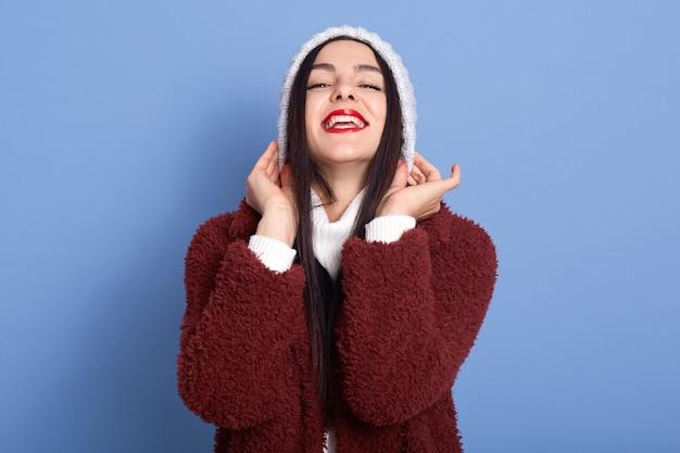 Garota de cabelos escuros coloca um chapéu de inverno em um espaço azul isolado rindo