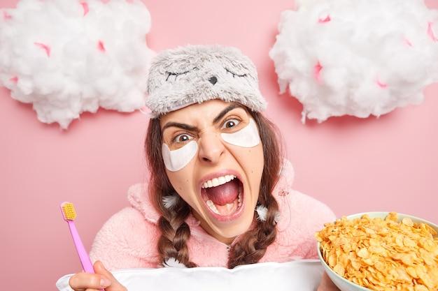 Garota de cabelos escuros zangada tem rotinas matinais, grita bem alto e mantém a boca aberta