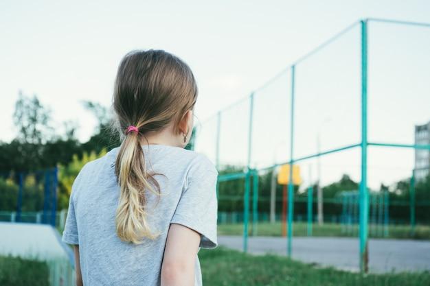 Garota de cabelos louros em uma camiseta cinza, olha para a quadra de basquete da escola. vista traseira