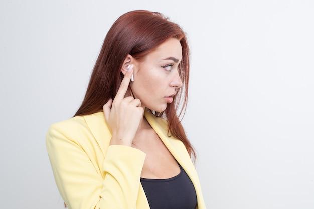 Garota de cabelos vermelhos em um terno amarelo ouvindo música em fones de ouvido bluetooth