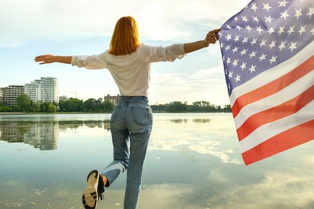 Garota de cabelos vermelhos segurando a bandeira nacional dos eua nas mãos dela. mulher jovem positiva comemorando o dia da independência dos estados unidos.