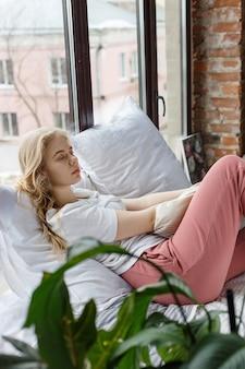 Garota de calça de pijama rosa, camiseta branca, sentada na cama com travesseiro perto da janela