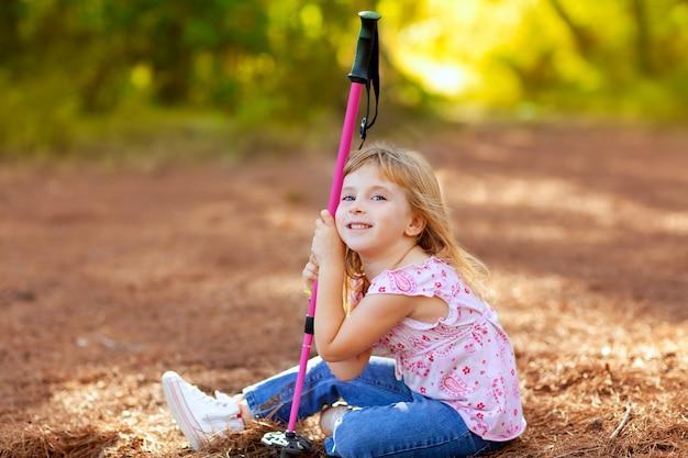 Garota de caminhadas garoto cansado sentado na floresta de outono