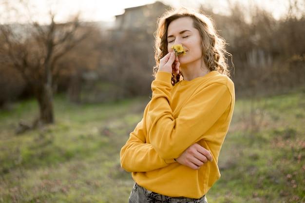 Garota de camisa amarela, cheirando uma flor