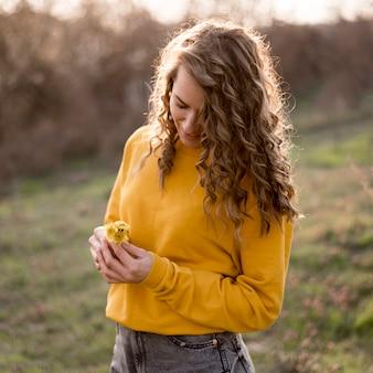 Garota de camisa amarela, segurando uma flor