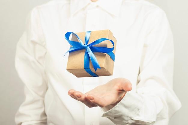 Garota de camisa branca pega um presente voador. conceito de receber um presente.