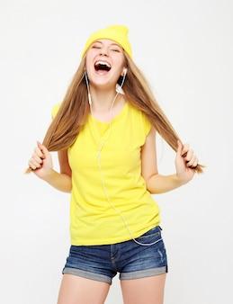 Garota de camiseta amarela dançando com a expressão do rosto inspirado.