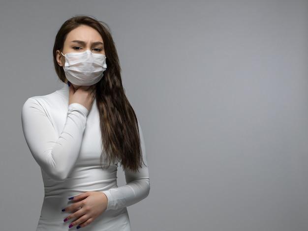 Garota de camiseta branca, segurando a garganta na máscara protetora branca