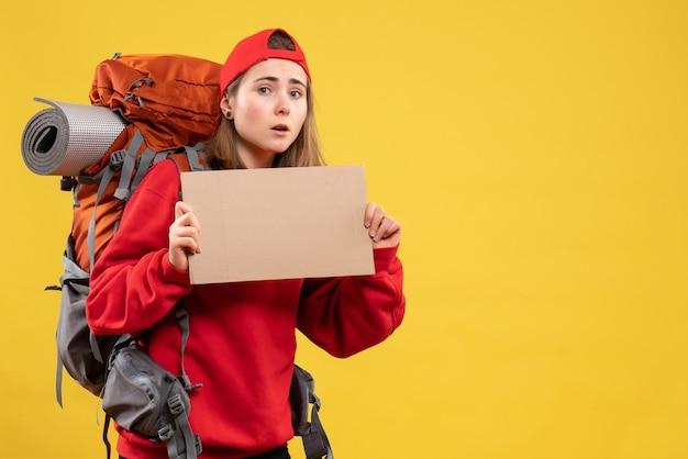 Garota de carona em vista frontal com mochila segurando um papelão em branco