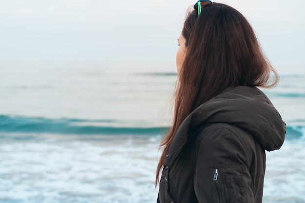 Garota de casaco quente olhando para o mar enquanto caminhava na praia na primavera