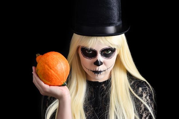Garota de caveira de açúcar com loira de chapéu preto com abóbora