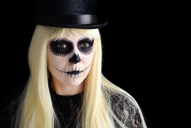 Garota de caveira de açúcar com loira de chapéu preto, studio um tiro. copie o espaço.