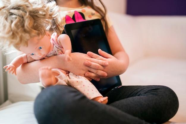 Garota de colheita com boneca e tablet
