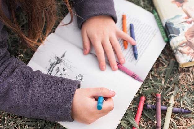 Garota de colheita desenho no caderno no chão