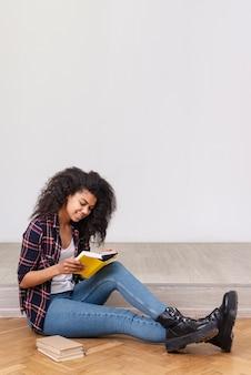 Garota de cópia-espaço concentrada na leitura