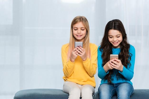 Garota de cópia-espaço usando celulares
