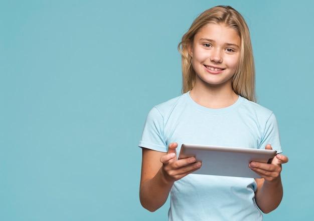 Garota de cópia-espaço usando tablet