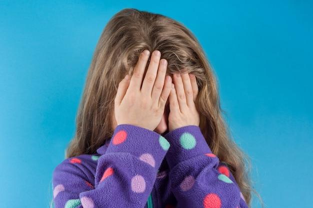 Garota de criança cobriu o rosto com as mãos
