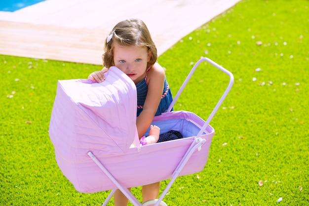 Garota de criança criança brincando com carrinho de bebê na relva verde