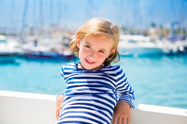 Garota de criança criança em barco de marina em férias de verão