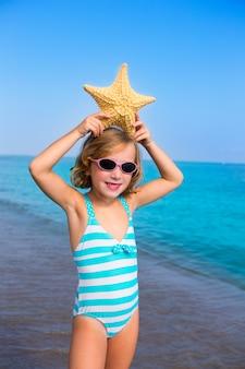 Garota de criança criança em férias de praia verão com estrela do mar