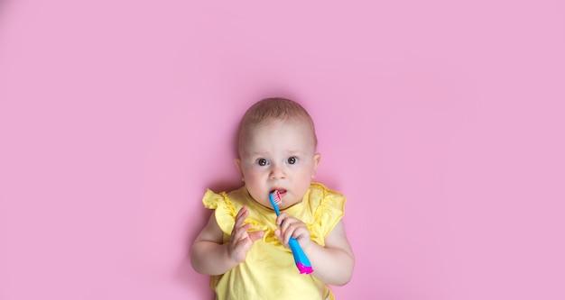 Garota de criança criança escovando os dentes no fundo rosa. cuidados de saúde, higiene dental, pessoas e conceito de beleza. maquete, espaço livre. Foto Premium