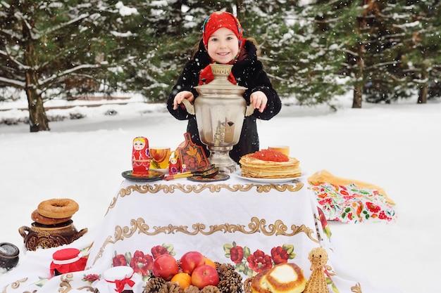 Garota de criança em um casaco de peles e em um lenço no estilo russo, segurando um grande samovar nas mãos
