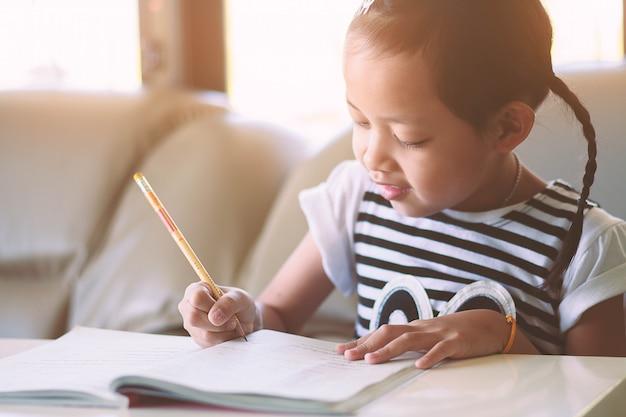 Garota de criança escrevendo no livro com sorriso. foco seletivo