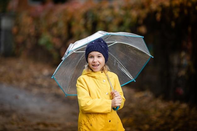 Garota de criança na jaqueta amarela e chapéu azul escuro com guarda-chuva transparente no parque outono