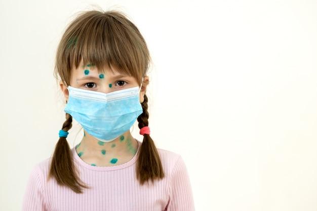 Garota de criança vestindo azul máscara médica protetora doente com varicela, vírus do sarampo ou rubéola com erupções no corpo. proteção infantil durante epidemia de coronovírus. conceito de contágio covid-19.