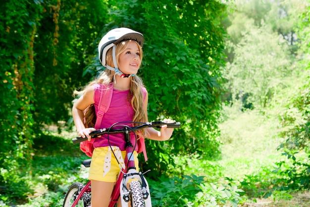 Garota de crianças andando de bicicleta ao ar livre na floresta sorrindo