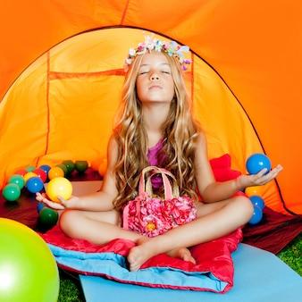 Garota de crianças dentro da barraca de acampamento relaxante com yoga