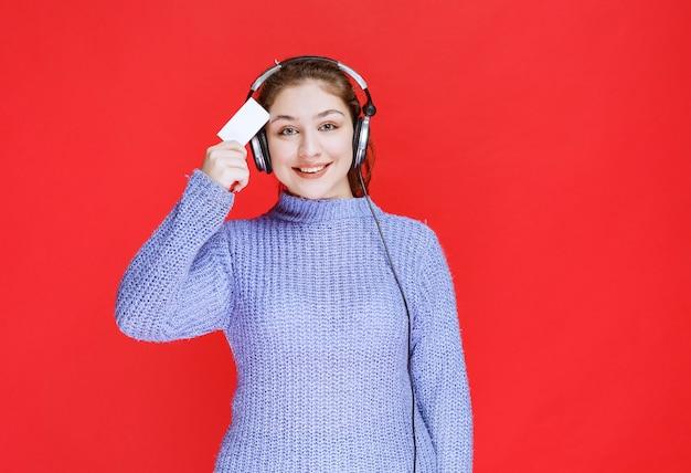 Garota de dj com fones de ouvido, apresentando seu cartão de visita.