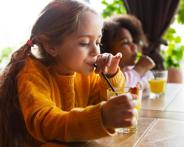 Garota de dose média bebendo suco