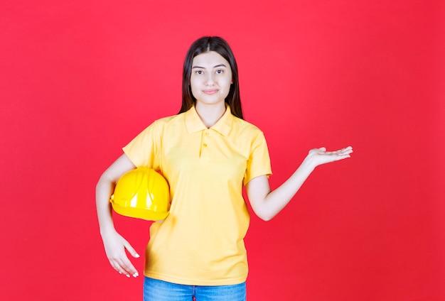 Garota de engenheira em dresscode amarelo segurando um capacete de segurança amarelo.