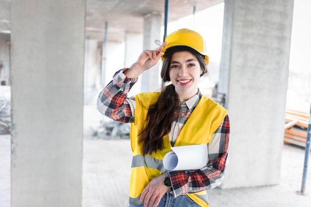 Garota de engenheiro de construção com desenhos na mão
